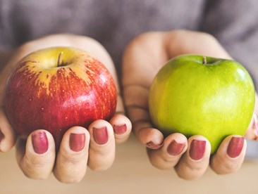 Two apples being held side by side for comparison