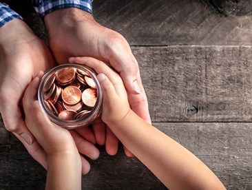 Father handing coins to child symbolizing transfer or wealth